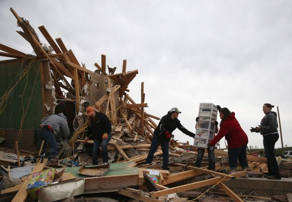 Volunteers help clean debris at the site of a home that was destroyed in Vilonia, Ark. Some 50 twisters were reported in the region in a 24-hour period from Monday into Tuesday, meteorologists say.