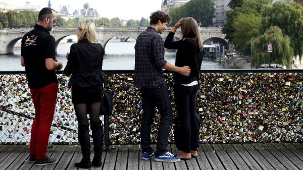 Couples stand on the Pont des Arts, Paris' iconic footbridge over the Seine river, where thousands upon thousands of padlocks bearing love messages are attached to the railing, on Aug. 30, 2013.