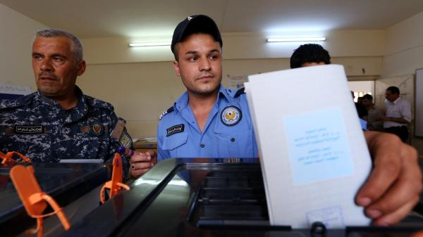 A Kurdish Iraqi policeman in the northern Kurdish city of Erbil casts his ballot Monday in special voting ahead of Wednesday's election.