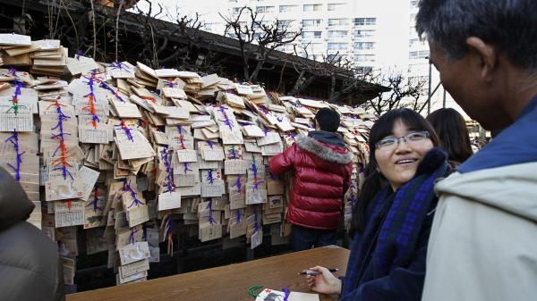 Saori Akizuki, 18, talks to her father, Hiroshi, as she writes her wish to pass a college entrance exam on a wooden plaque at a Tokyo shrine in 2011.