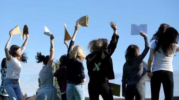Students in Manchester, England, celebrate the results of their college entrance exams.