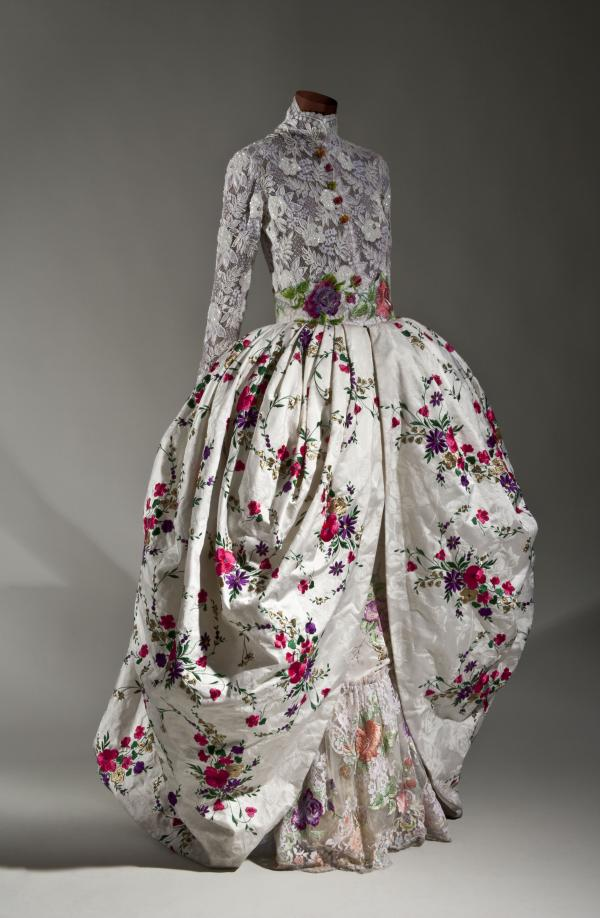 "A bridal gown made of cotton/synthetic blend lace, embroidered silk, plastic ""pearl"" beads and sequins and glass beads from French designer Emanuel Ungaro, 1996-97."