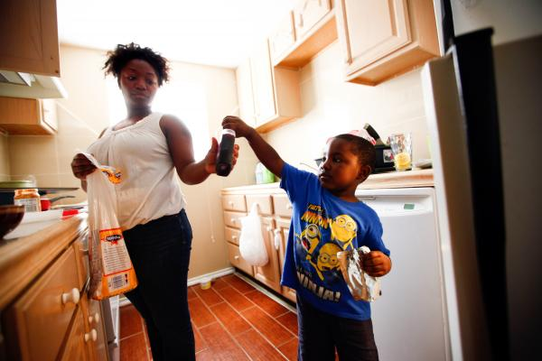 Shartara Wallace helps her son James, 4, make a peanut butter and jelly sandwich at their home in Tulsa, Okla. Wallace is working toward a nursing degree through the Community Action Project's Career Advance Program.