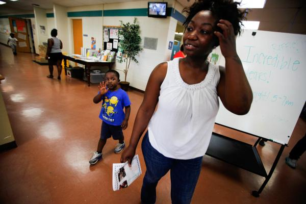 Shartara Wallace picks up her son James, 4, from preschool. Sometimes she takes her two children to community college with her if she needs to return to campus to study.