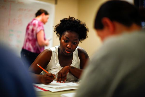 Shartara Wallace works out a problem in a basic math class at Tulsa Community College. She's tried going back to school before, but hopes the support of the Career Advance program will help her finish this time.