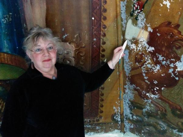 Art conservator Connie Silver points to a section of the mural that's been cleaned of its grime.