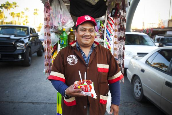 Tijuana street vendor Fidencio Rodriguez displays a freshly made batch of <em>tostilocos,</em> a unique border snack making inroads in the U.S.