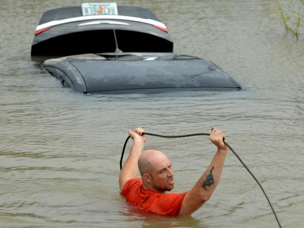 Michael Harrell of J&J Towing attaches a tow cable to a car that was swept off the road by torrential rains in Pensacola, Fla., on Wednesday.