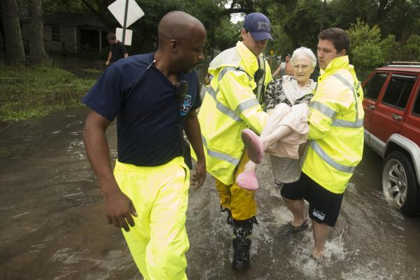 Winnie Bunting is carried to an ambulance after being rescued from her flooded home in Pensacola.