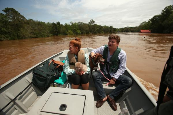 In Fairhope, Ala., Marine Police rescued Sarah and Hunter Anderson and their two dogs from their home on the Fish River, which has swelled to historic levels.