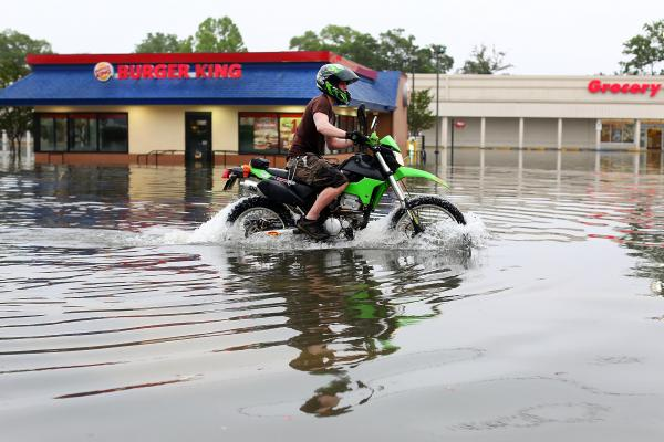 A man rode a motorcycle on a flooded street in Pensacola. Wednesday marked the single rainiest day ever recorded in the city. <br /><br />