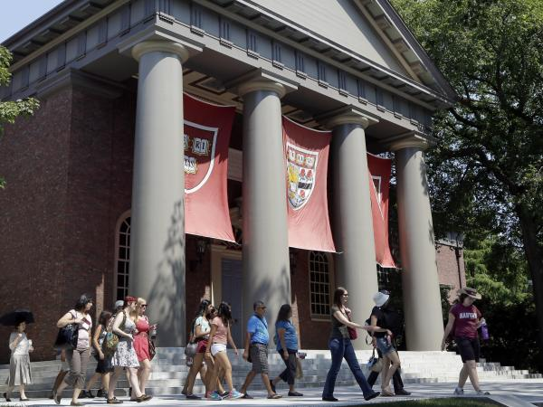 People tour the campus of Harvard University in Cambridge, Mass., in 2012. Harvard was one of 55 institutions on the Education Department's newly released list.