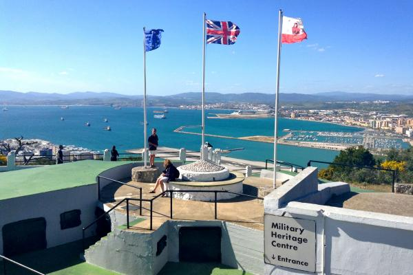Flags of the European Union, Great Britain and Gibraltar (left ot right) fly over a former military post in Gibraltar.