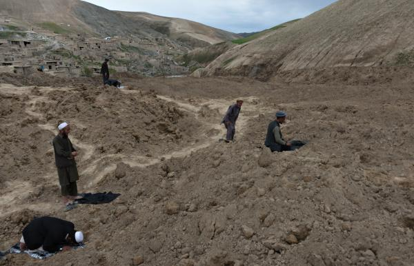 Afghan villagers pray at the site of a landslide in Abi-Barik Saturday. Rescuers searched in vain for survivors of the disaster, which is feared to have killed more than 2,000 people.
