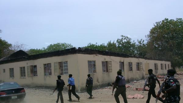 Nigerian security forces walk past the burned-out high school in the northeastern town of Chibok, where schoolgirls were seized on April 14. Dozens of the girls managed to escape by jumping from the back of an open truck or hiding in dense forest.