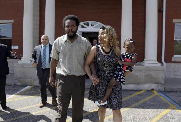 "Cornealious ""Mike"" Anderson walks out of the Missouri County Courthouse along with his wife, LaQonna Anderson, their daughter Nevaeh, 3, and his attorney Patrick Megaro on Monday in Charleston, Mo."