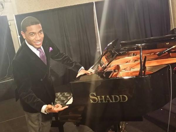 Pianist Christian Sands stands with a Shadd Piano at the Mid-Atlantic Jazz Festival in 2014.