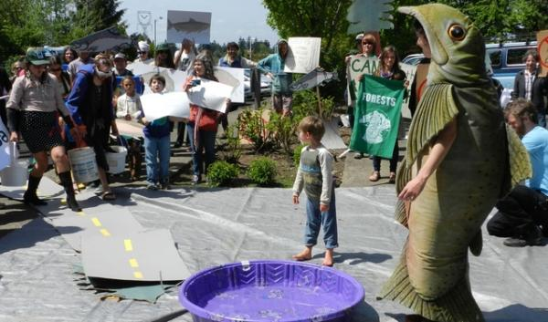 Demonstrators used a small swimming pool to illustrate how forest roadbuilding would put mud in the Collawash River and harm salmon.