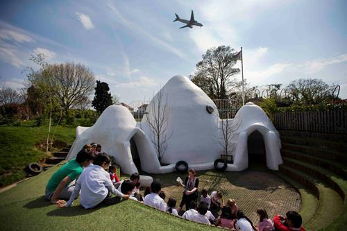 British schoolchildren outside an adobe hut that was built so they could play in a less noisy place when jets fly overhead. The kids go to school near London's Heathrow Airport, where a planes takeoff and land every 90 seconds.