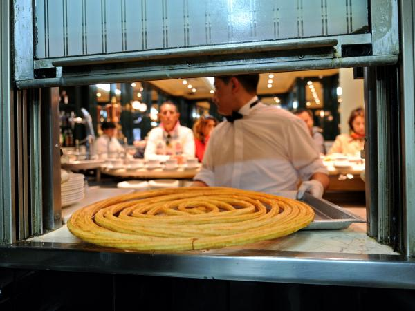 A fried churro makes it way through the window of a shop in Madrid.