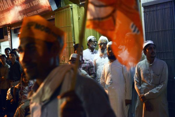 A group of Muslim men stand aside, waiting for a car convoy carrying candidate Narendra Modi to pass in the streets of Varanasi last week.