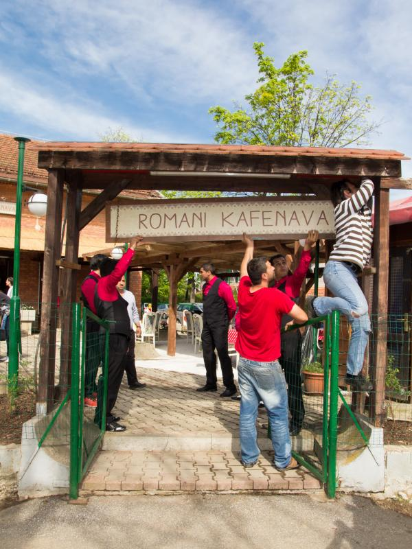 Workers hang the sign at Romani Kafenava ahead of the restaurant's opening.