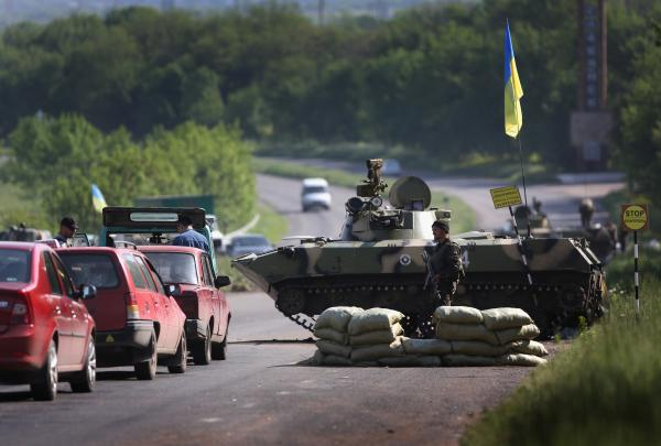 Ukranian soldiers stop cars at a highway checkpoint near Slovansky, Ukraine, on Tuesday.