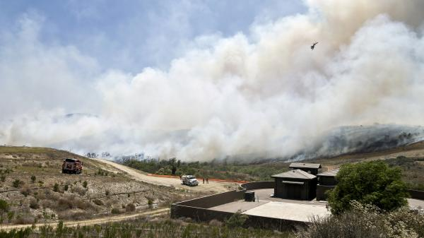 Smoke rises from a canyon in San Diego where a wildfire raged on Tuesday. County officials say they're investigating how a rogue message appeared in their emergency app.