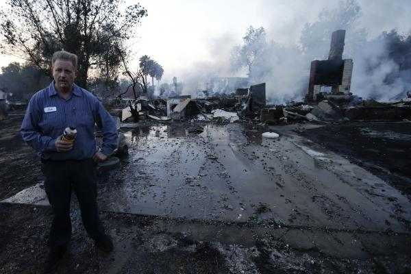 Jack Whitlang stands in front of his aunt's home, which burned to the foundation in the Escondido Fire.