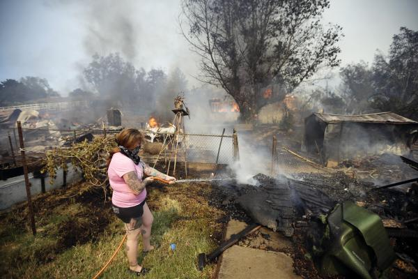 A woman douses debris around her home as her neighbor's home burns Thursday in Escondido.