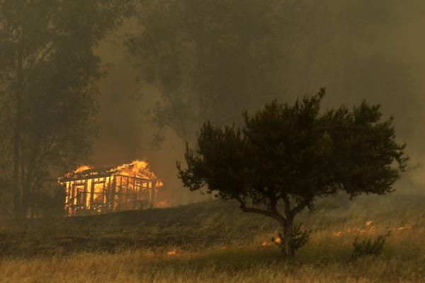 Fire engulfs a structure Thursday in Escondido, Calif. One of the nine wildfires burning in San Diego County suddenly flared Thursday afternoon and burned close to homes, triggering thousands of new evacuation orders.