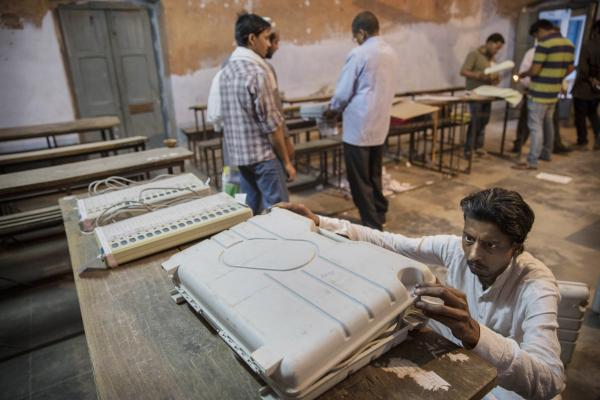 An Indian election worker closes up an electronic voting machine before sealing it after the final polls closed a polling station on May 12 in Varanasi, India.