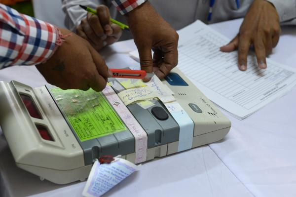 An Indian election commission officer cuts the seal of an electronic voting machine at a counting center in New Delhi on May 16.