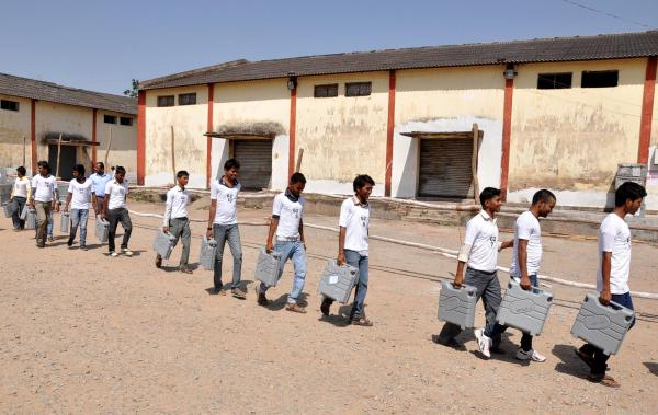 Indian election officials carry electronic voting machines towards a counting center in Ranchi on May 16.