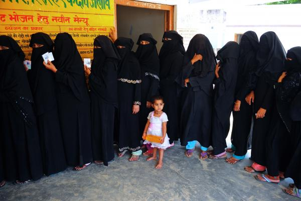 A child looks on as Muslim women wait in line to cast their votes at a polling station in Azamgarh, India on May 12.