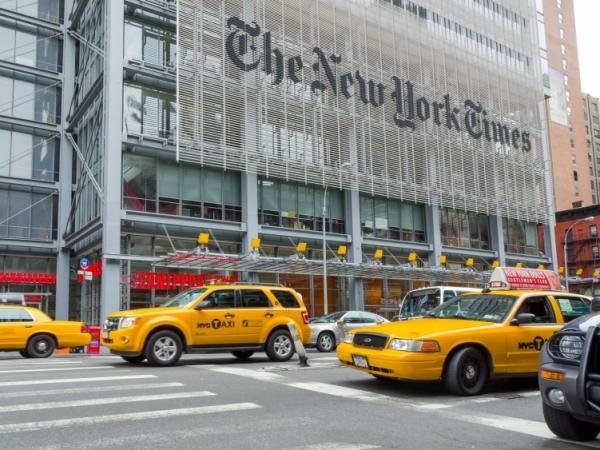 Taxis speed past the headquarters of the <em>New York Times.</em>
