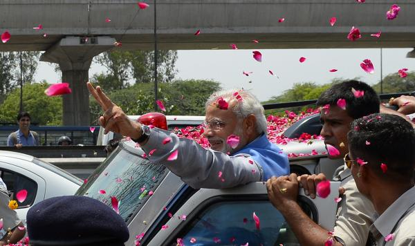 Hundreds of flag-waving supporters mob Modi as he arrives in New Delhi.