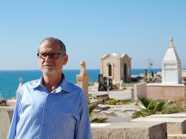 "Peter Habash, an Arab Christian, stands at a Christian graveyard in Jaffa. ""We have no connection"" with migrant or Russian Christians, he says."
