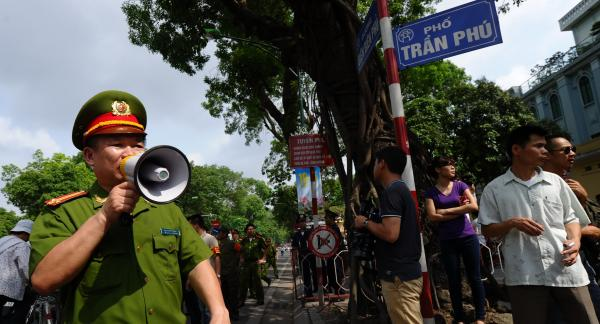 Policemen ask people to leave a street near to the Chinese embassy in Hanoi on Sunday. A call for further anti-China protests appeared to have fizzled in the capital, with authorities deploying heavy security around the Chinese embassy and other suspected protest sites.