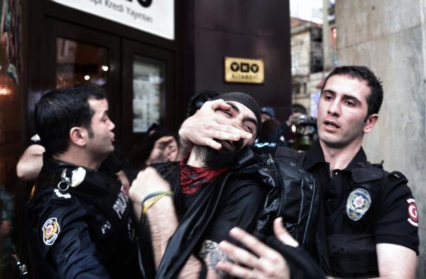 Riot police detain a protester as they use water cannons and teargas to disperse people who were protesting the Soma mine accident that killed 301 miners, in Istanbul, Turkey, on Saturday.
