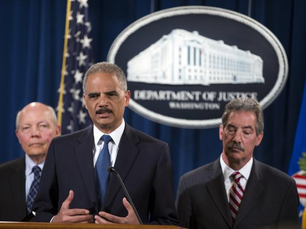 Attorney General Eric Holder speaks during a news conference at the Justice Department on Monday. Holder announced that Credit Suisse had agreed to pay $2.6 billion in a criminal settlement. With him are IRS Commissioner John Koskinen (left) and Deputy Attorney General James Cole.