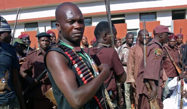 Armed hunters gather before looking for around 300 abducted school girls in Maiduguri, Nigeria, May 18, 2014. Hundreds of hunters armed with homemade rifles, poisoned arrows and amulets say their spiritual powers can lead them to the nearly 300 schoolgirls abducted by Islamic extremists. (Haruna Umar/AP)