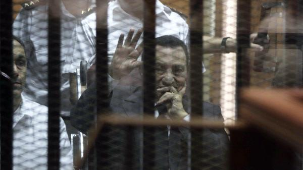 Ousted Egyptian President Hosni Mubarak, sitting in a defendants cage, waves during a court hearing Wednesday. He and two sons were sentenced to jail on corruption charges.