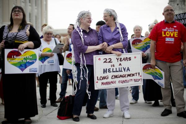 Peg Welch, center left, and her wife Delma Welch gather with others at a gay marriage rally on the steps of the state Capitol Tuesday, May 20, 2014, in Harrisburg, Pa. Pennsylvania's ban on gay marriage was overturned Tuesday by a federal judge in a decision that makes same-sex marriage legal throughout the Northeast. (Matt Rourke/AP)