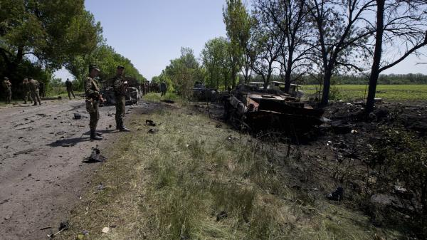 Ukrainian soldiers inspect the site of a gunfight near the village of Blahodatne in eastern Ukraine Thursday. At least 11 Ukrainian troops were killed and about 30 others were wounded when Pro-Russians attacked a military checkpoint.