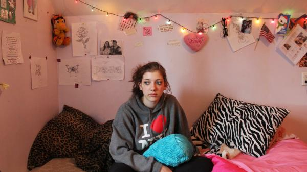 Desiree Wieczorek sits in a bedroom she now shares with her sister. The best part of living in a house after being homeless for five months, she says, is the warm showers.