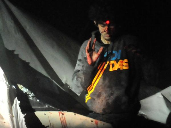 Boston bombings suspect Dzhokhar Tsarnaev on April 19, 2013, as he emerged from a boat stored in a Watertown, Mass., backyard. The red dot of a police sharpshooter's laser sight can be seen on his forehead.