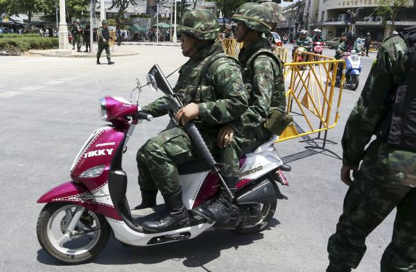 Thai soldiers patrol on a scooter Friday near the Democracy Monument in Bangkok. Thailand's ruling military summoned leaders of the ousted government to meetings today. Restrictions on TV broadcasts have led Thai citizens to ask for more variety.