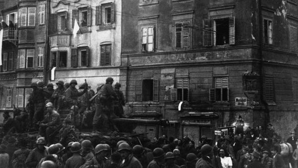 Crowds gather around the lead tank of the 1st Battalion 400th Infantry task force, and 103rd Cactus Division, after soldiers entered without resistance in Innsbruck, Austria, on May 19, 1945.
