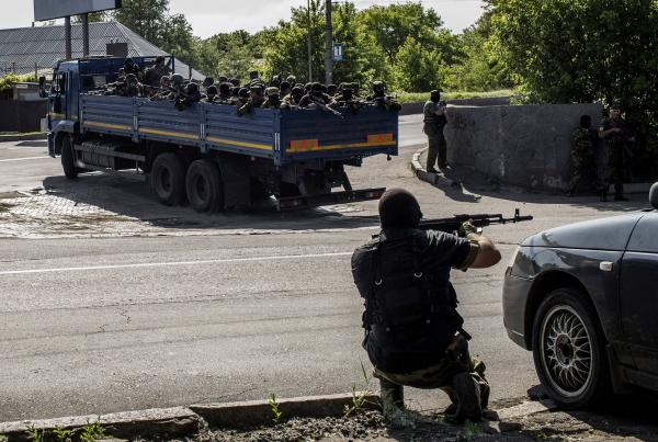 A pro-Russian fighter takes position behind a car as a truck full of rebel fighters heads toward a battle with Ukrainian forces near the airport in Donetsk Monday. The rebels say more than 30 of their number were killed in the violence.